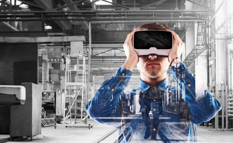 Hipster man in denim shirt wearing virtual reality goggles. Welding factory.
