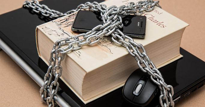 Notebook, Smartphone und Buch in Ketten