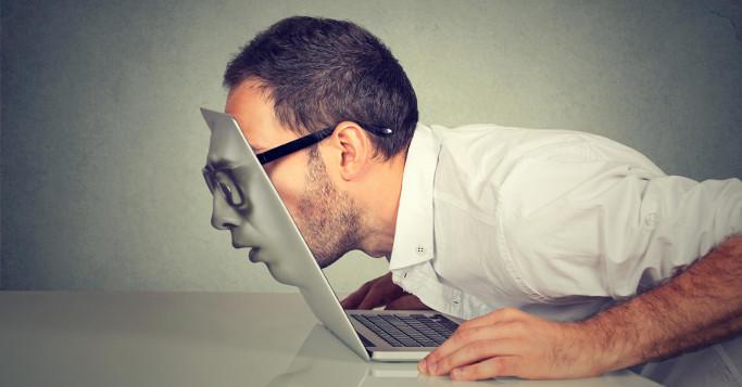 man watching through his macbook becoming a machine