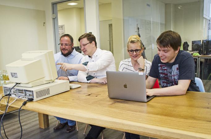 Die dotSource im Wandel der Zeit. Mitarbeiter 1 und 2 - beide Gründer der dotSource - mit Mitarbeiter 100 und 200 an einem Tisch schauen in einen alten Computer und ein Laptop.