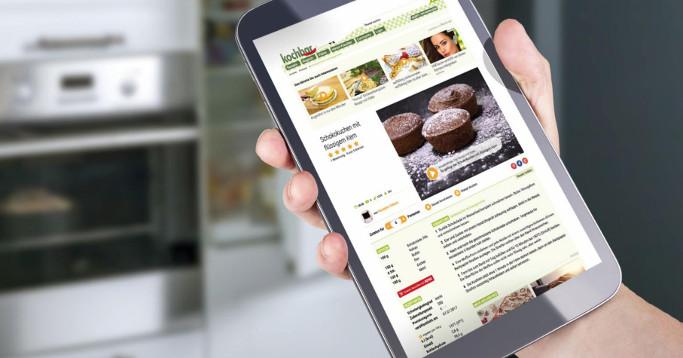 Tablet mit Rezeptseite vor smartem Kühlschrank