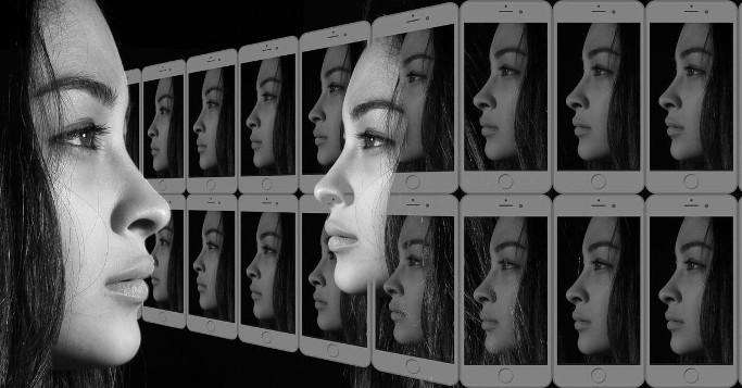 junge Frau mit Handyreihe als Spiegel