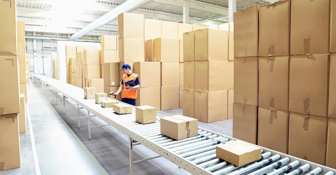 Mann scant Pakete im Logistikzentrum