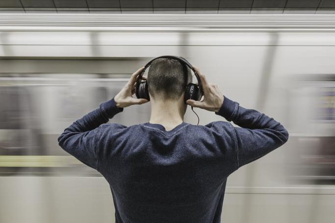 junger Mann in Underground-Station mit Kopfhöhrern