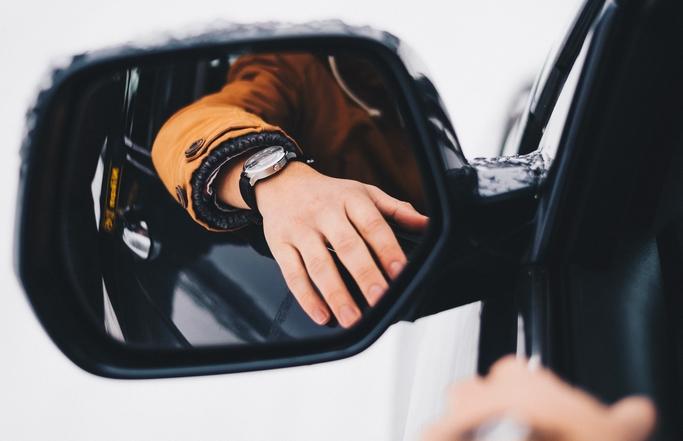 Uhr an Arm auf einem Auto vor einem Autospiegel