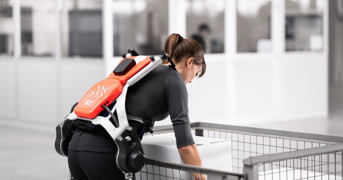 Frau trägt mit einem Exoskelett von German Bionic eine Kiste